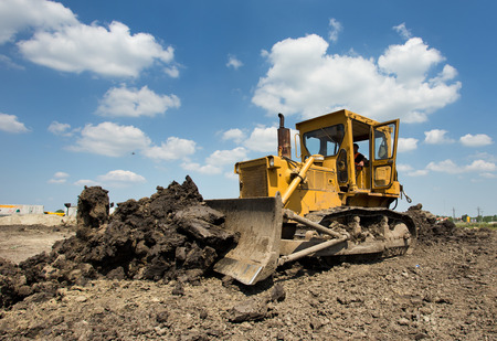 Old yellow bulldozer with caterpillar moving ground with scoop. Blue sky and white clouds in background