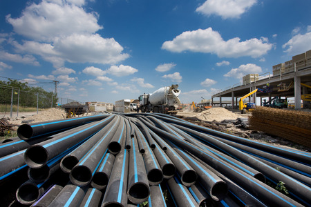 Close up of rubber pipes on pile and other construction material and equipment at building site Archivio Fotografico