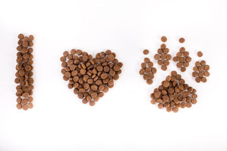 granule: Text I love dogs shaped from doggy dry food into heart and paw. Isolated on white background