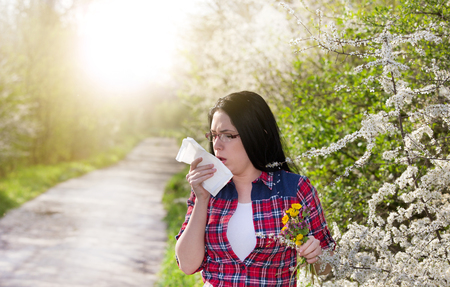blowing nose: Pretty young woman holding flowers and tissue in other hand because of allergy and sneezing Stock Photo