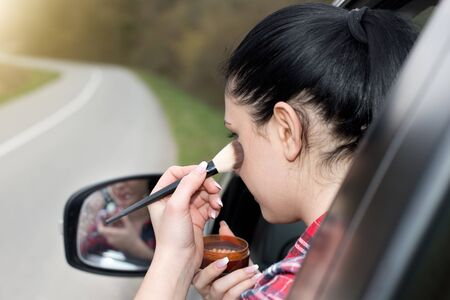 Rearview of beautiful girl applying makeup in the car looking at mirror through window Stock Photo