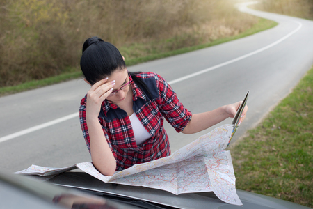 Young pretty woman looking at map on hood of the car beside road. Lost on trip, worried face Stock Photo