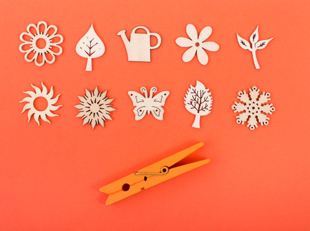card making: Decoration of wooden element in shapes from nature on orange background as craft