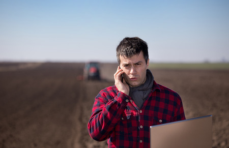 Young farmer with laptop talking on cell phone in field while tractor harrowing in background. Agricultural works in spring Stock Photo