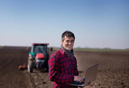 Young farmer working on laptop on field with tractor in background harrowing soil. Agricultural works in early spring
