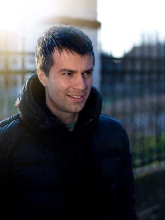 Portrait of smiling attractive man in winter jacket beside old fence Stock Photo