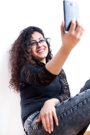 Young preety woman holding smartphone and taking selfie against white wall Stock Photo