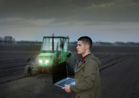 harrowing: Young farmer with laptop standing in field with tractor harrowing in background