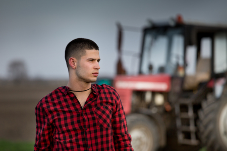 harrowing: Young farmer in plaid shirt standing in front of tractor in field