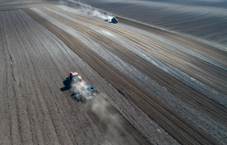 Aerial view of two tractors harrowing arable land shot from drone