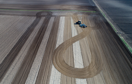 Aerial view of tractor harrowing arable land shot from drone
