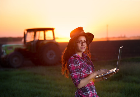 agronomist: Young country woman with hat holding laptop in front of tractor on field at sunset Stock Photo