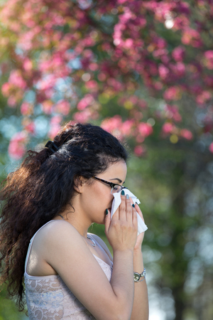 alergenos: Young woman sneezing and blowing nose in tissue in front of blooming tree. Seasonal allergens affecting people