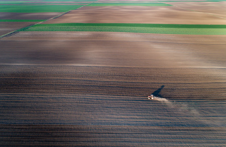 harrowing: Aerial view of tractor harrowing arable land shot from drone