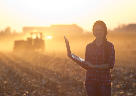 Young woman with laptop standing in field at sunset and looking with tractor baling in background