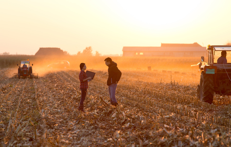 Farmer woman with laptop and landowner talking on field with tractor working in background at sunset