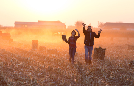 Farmer woman with laptop and landowner walking and waving hands on field with tractor working in background at sunset