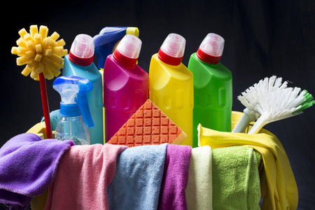 cleaning service: Plastic basket full of cleaning supplies and equipment isolated on black background Stock Photo