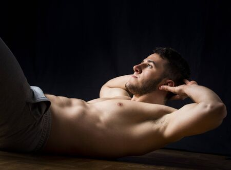 Handsome young man doing six pack exercise on parquet with black background