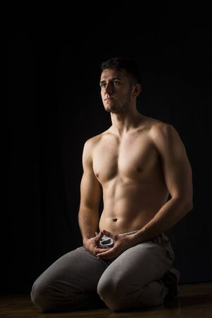 healing chi spiritual: Handsome muscular man relaxing after sport and meditating on floor. Black background