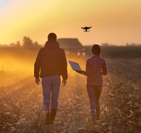 Mujer del granjero con el ordenador portátil y terrateniente que recorre en campo con aviones no tripulados volando por encima de tierras de cultivo al atardecer