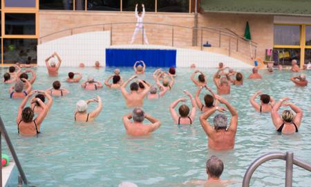 プールで運動をしている高齢者の大規模なグループ 写真素材
