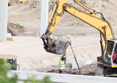 Excavator working at construction site with workers attaching load to bucket Stock Photo
