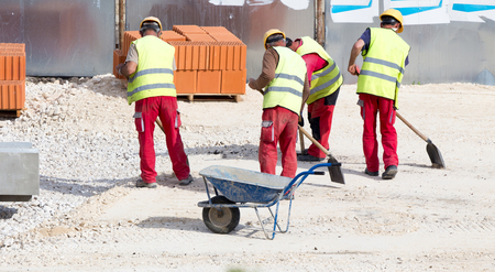 Group of construction workers cleaning building site and loading wheelbarrow with gravel Archivio Fotografico