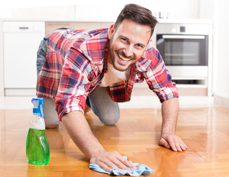 Happy handsome man wiping parquet floor, smiling and looking at camera. Husband housekeeping and cleaning concept. Home interior and kitchen in background Stock Photo