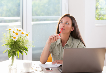 woman on phone: Pretty young woman daydreaming in front of laptop. Sitting at table in big sunny room with flowers Stock Photo
