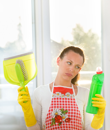 Tired young woman with apron and rubber gloves holding bottle with disinfectant and dust pan. Housewife expressing bad emotions about chores