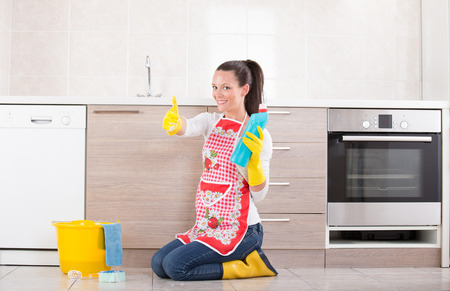 Satisfied woman kneeling on tiled floor beside bucket in kitchen. Showing bottle of cleaning product and thumb up. Stock Photo