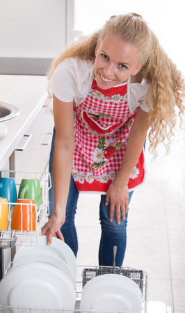 lavar platos: Mujer rubia joven sonriente que apila dishware en el lavaplatos en cocina con el fondo blanco. Expresión alegre sobre las tareas domésticas