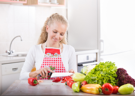 Beautiful blonde woman cutting vegetables on table in kitchen. Preparing fresh food. Healthy lifestyle concept