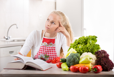 Pretty young blonde woman reading recipe book and preparing vegetables for lunch. Bright kitchen in background Stock Photo