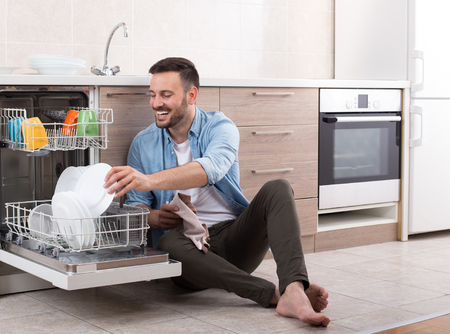 Happy handsome man unloading dishwasher and enjoying in housework. Husband doing chores in kitchen
