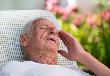 Old man lying in easy chair in garden and holding hand on forehead because of pain