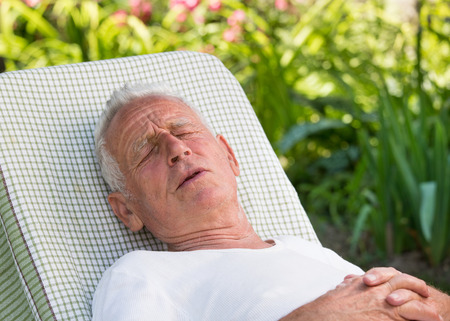 Old man with pains lying on easy chair in garden with flowers in background Stock Photo