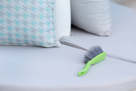 Cleaning brush on the sofa on terrace of cafeteria Stock Photo