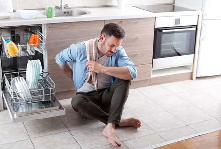 Handsome young man with back pain sitting on tiled floor beside open dishwasher machine in kitchen. Husband doing chores, tired of housework