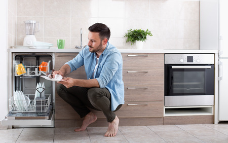 doing chores: Young handsome man unloading dishwasher and wiping plate. Husband doing chores in kitchen Stock Photo