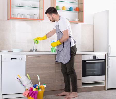 エプロンと保護手袋を持つ若いハンサムな男は、台所でシンクと蛇口を拭きます。ハウスクリーニングサービス