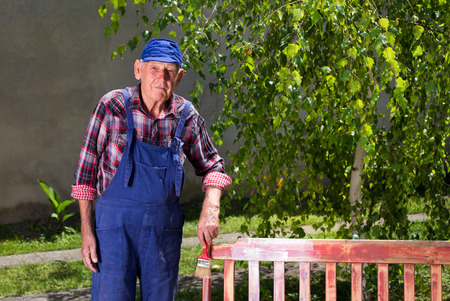 Portrait of senior man in overalls painting old bench in garden  after sandblasting. Repairing old furniture Stock Photo