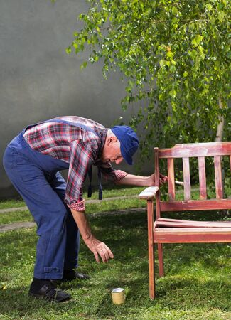Senior man in overalls painting old bench in garden after sandblasting. Repairing old furniture Stock Photo