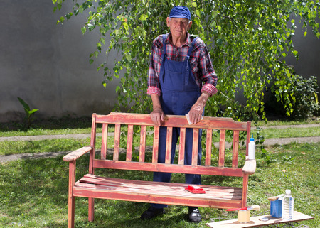 Portrait of senior man in overalls sandblasting old bench in garden and preparing it for painting