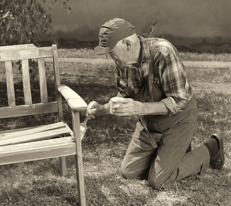 Senior man in overalls painting old bench in park after sandblasting. Repairing old furniture. Black and white image