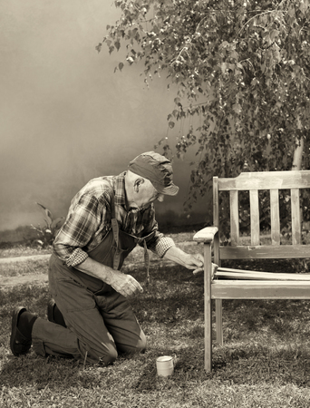Senior man in overalls painting old bench in park after sandblasting. Repairing old furniture. Sepia image technique