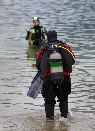 Divers with full equipment entering water in mountain lake