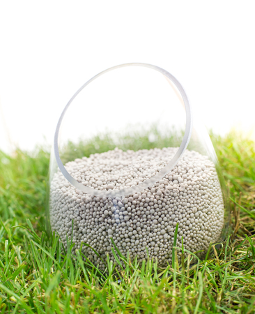 Close up of mineral fertilizer for soil in glass pot in the grass Stock Photo