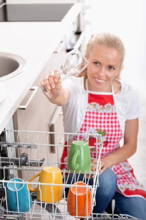 Pretty blonde woman holding wine glass high above dishwasher and checking cleanness Stock Photo